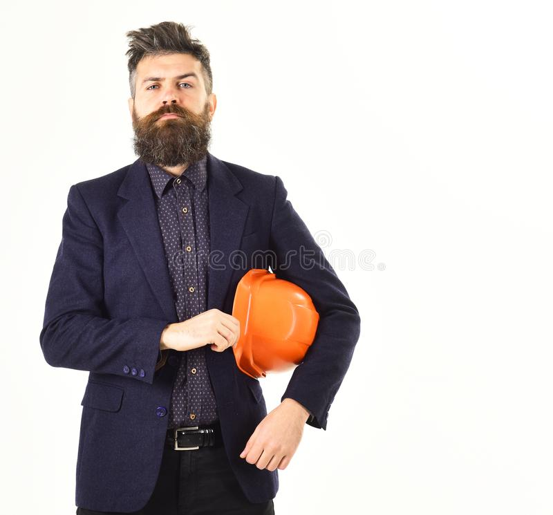 Team leader or construction manager with proud face. Bearded man holds helmet isolated on white background. Architect or site manager looks proud. Building royalty free stock photo