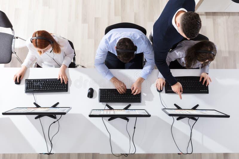 Team Leader Giving Training To Zijn Call centreexploitant stock afbeelding