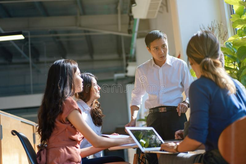 Team leader meeting with young asian employees in smart casual wear stock images