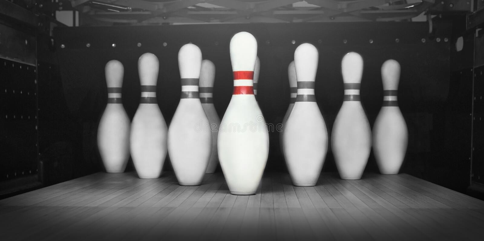 Team leader - one red bowling pin in front of others. Leadership concept - red bowling pin in front of black and white stock photo