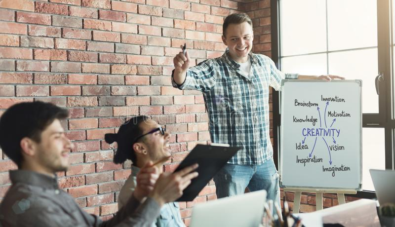 Team leader presenting creativity meaning to coworkers stock photo