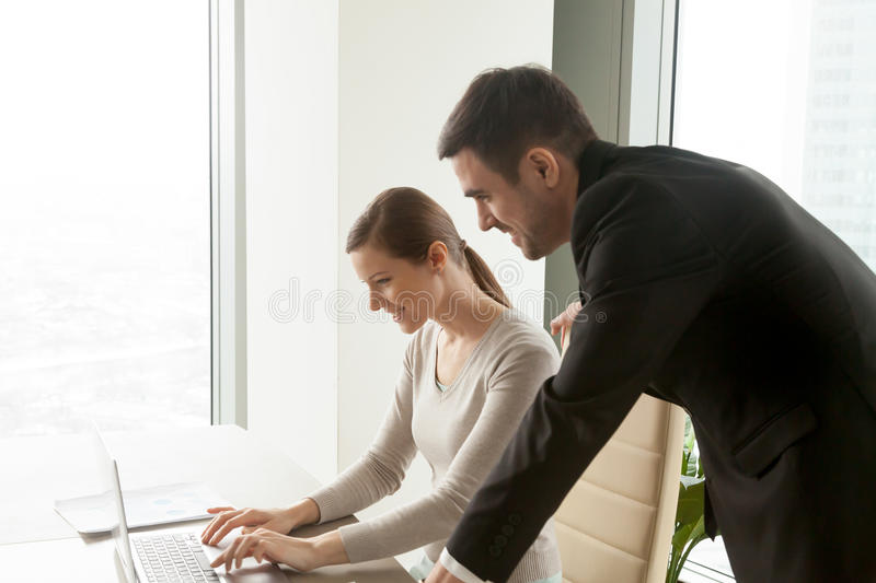 Team leader supervising employee working on laptop computer, bus. Smiling young intern working on laptop computer in office, listening to executive manager royalty free stock photos