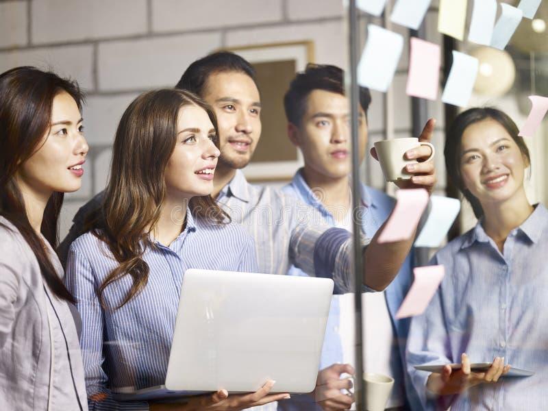Team les entrepreneurs asiatiques et caucasiens se réunissant dans le bureau photo stock