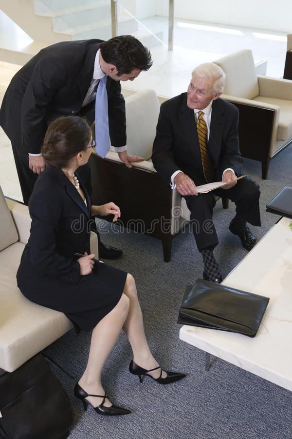 Team in lobby meeting to review paperwork. royalty free stock photo