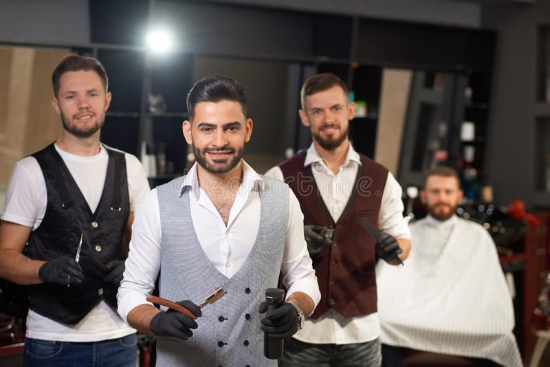 Team of male hairdressers looking at camera in barbershop stock photo