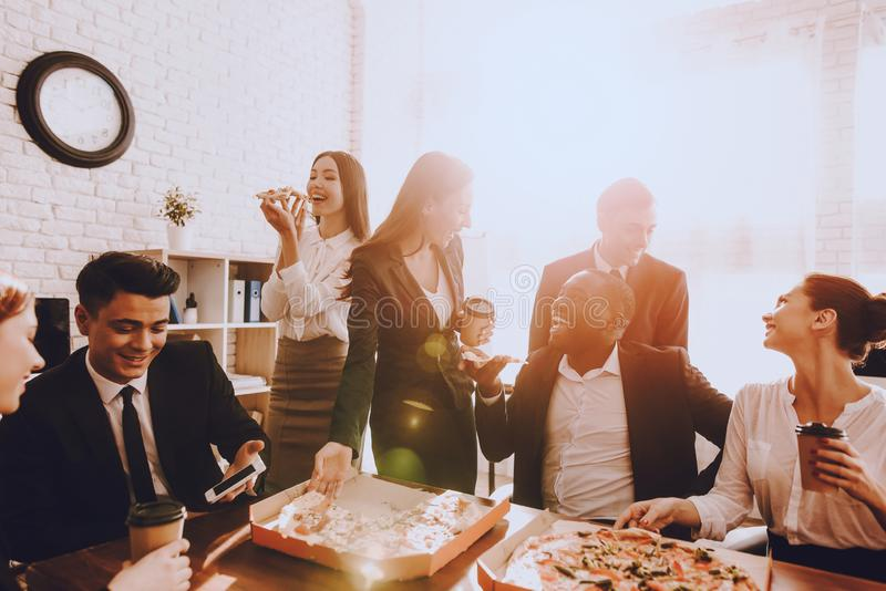 Team of Managers Have Lunch in Modern Office. Rest after Business Meeting. Modern Office Concept. Cooperation with Colleagues. Businessman with Team. Pizza in stock photo