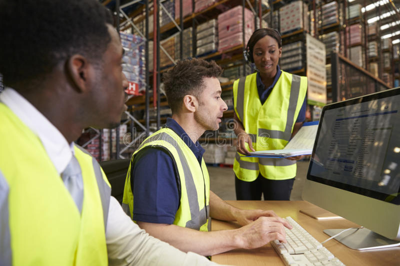 Team managing warehouse logistics in an on-site office stock images