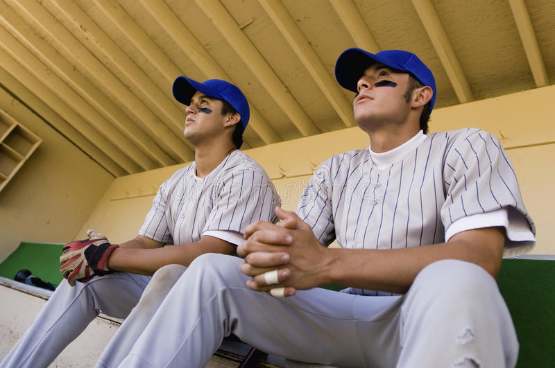 Team-Mates Sitting In Dugout stock photography