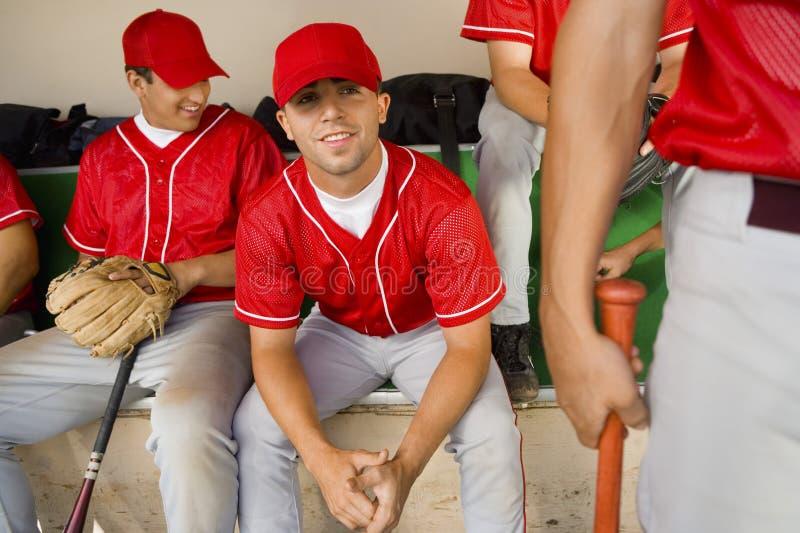 Team-mates van het honkbal in dugout stock foto's