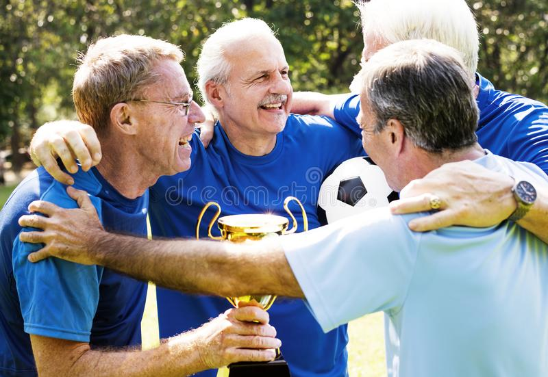 Team of mature football players winning the cup royalty free stock photos