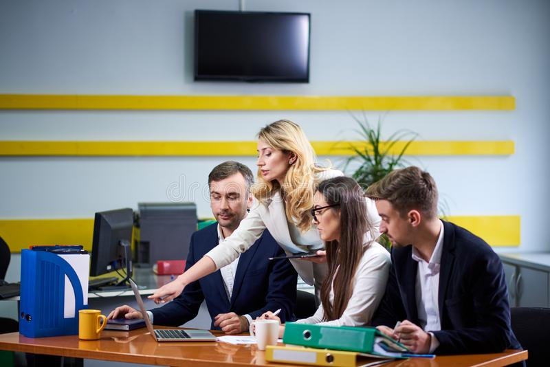 Team of mature women and men at meeting table discussing a business plan stock images