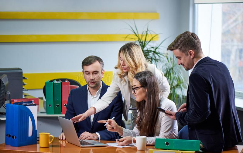 Team of mature women and men at meeting table discussing a business plan royalty free stock photo