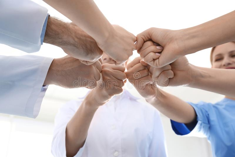 Team of medical doctors putting hands together on light background. Unity concept stock images