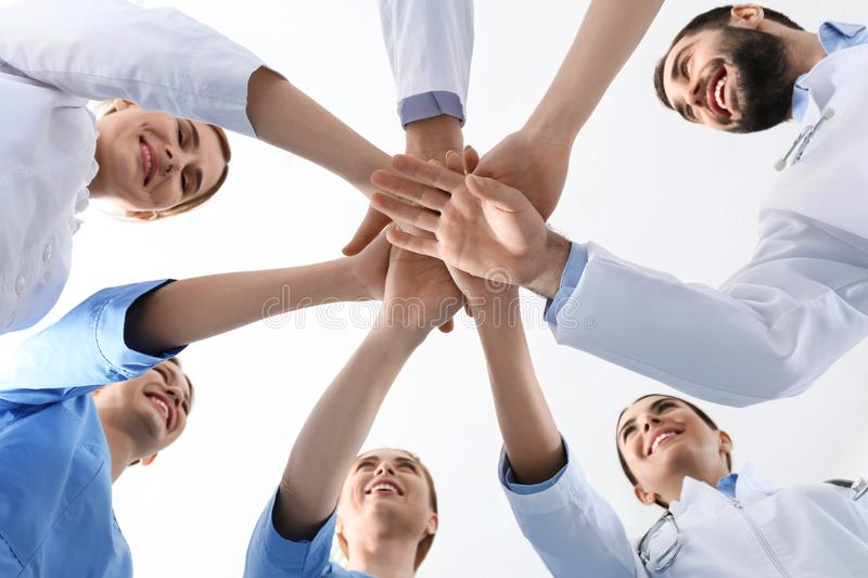 Team of medical doctors putting hands together on white background, closeup. Unity concept stock image