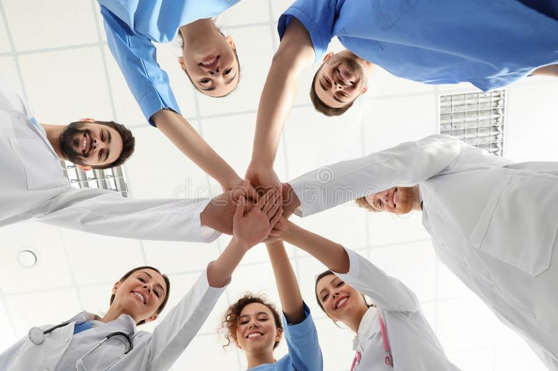 Team of medical workers holding hands together in hospitaд. Unity concept royalty free stock photography