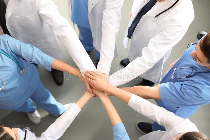 Team of medical workers holding hands together indoors, top view royalty free stock photography