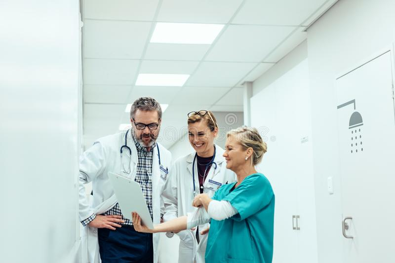Team of medics looking at medical report in hospital corridor royalty free stock photos