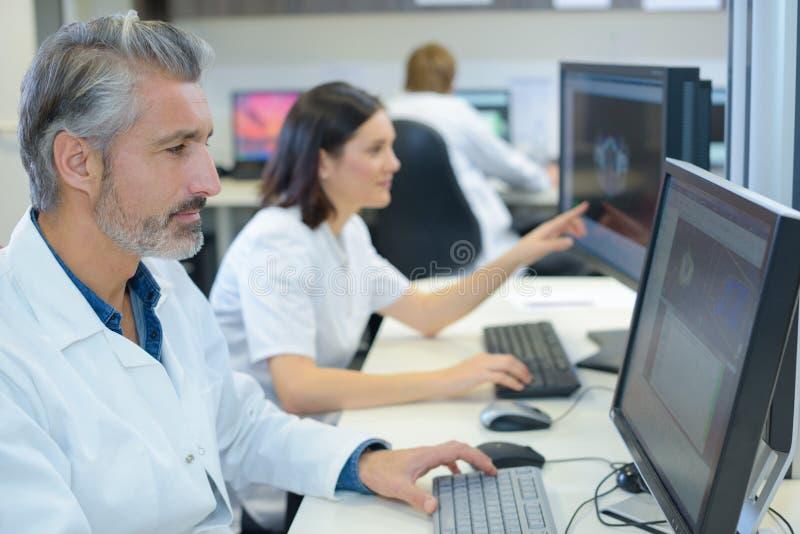 Team medische analisten die aan computers werken stock afbeeldingen