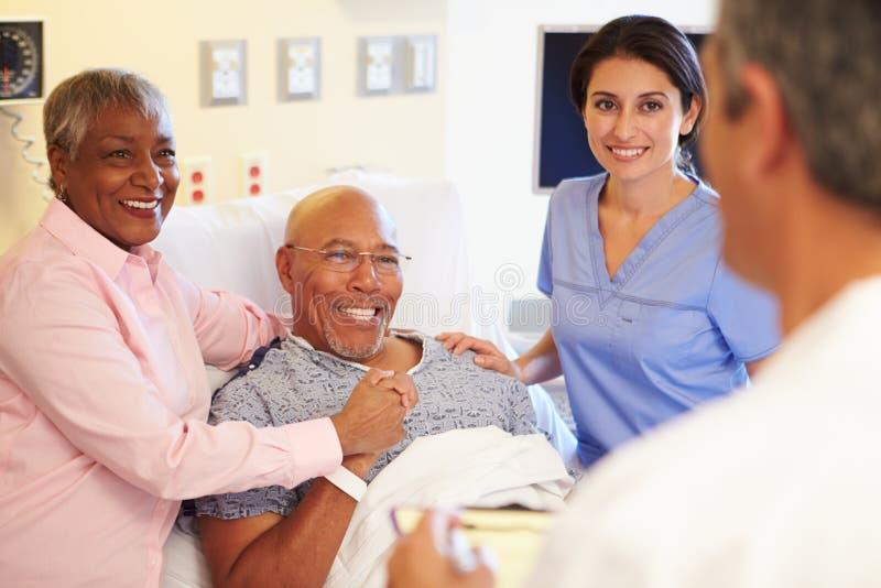 Team Meeting With Senior Couple medico nella stanza di ospedale fotografie stock