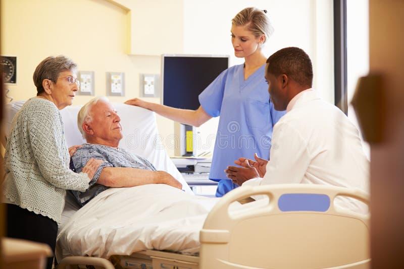 Team Meeting With Senior Couple medico nella stanza di ospedale fotografie stock libere da diritti