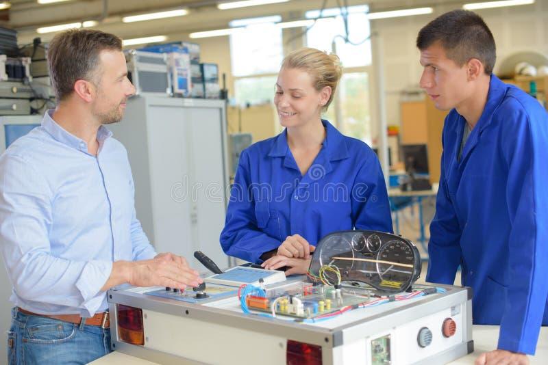 Team mekaniska teknikerer som i regeringsställning arbetar med nytt arkitektoniskt projekt royaltyfri bild
