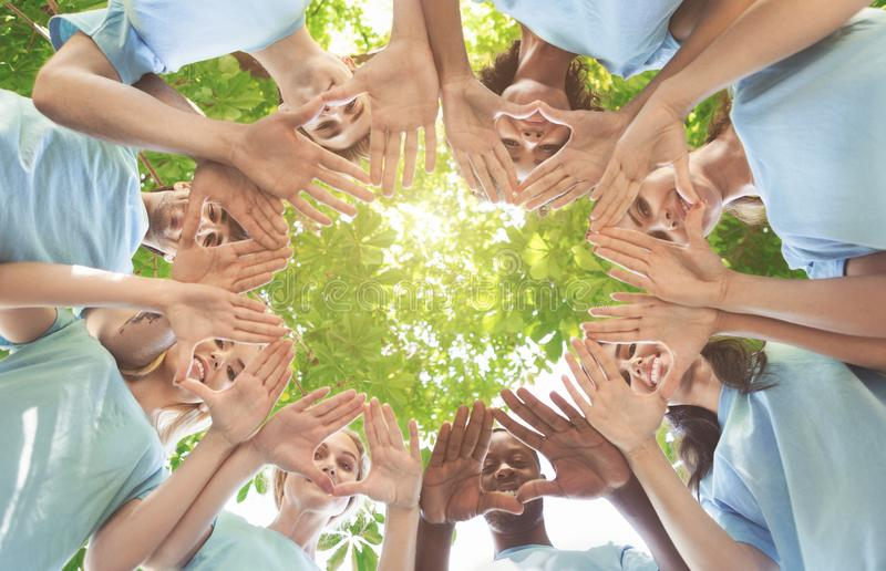 Creative team putting their hands together in circle. Team of millennial volunteers smiling at camera through palms, standing together in circle, view from below stock images