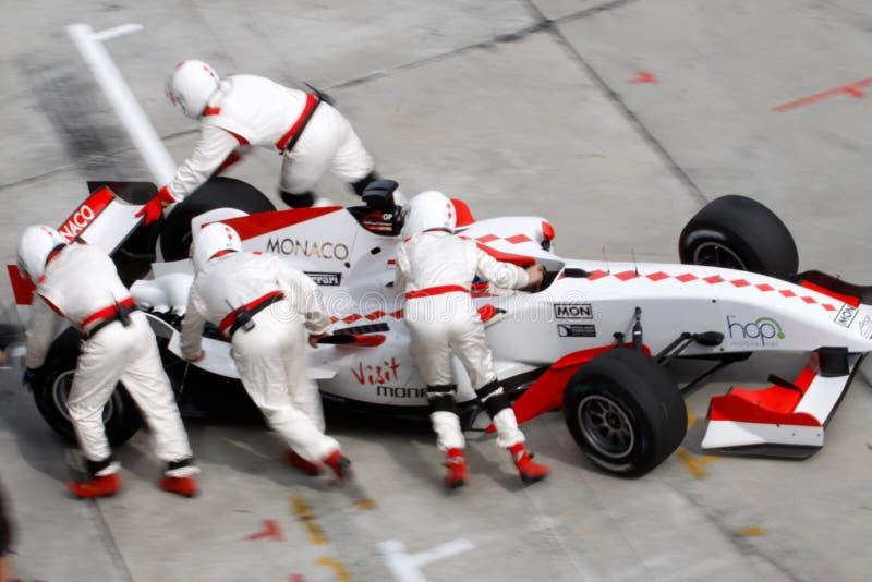Team-Monaco-Mechaniker, die zurück Auto drücken stockfotografie