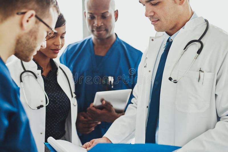 Team of multiracial doctors reading patient notes royalty free stock photos