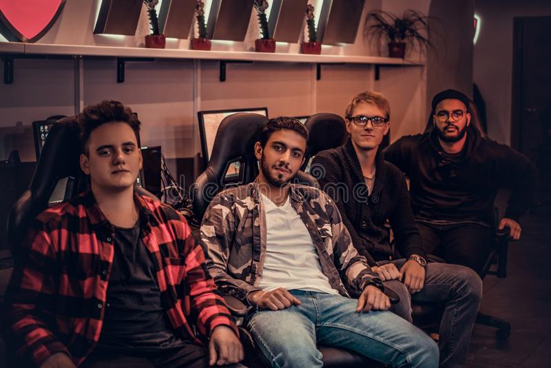 A team of multiracial teenage gamers sitting on gamer chairs and looking at a camera in a gaming club or internet cafe. Team of multiracial teenage gamers royalty free stock photo