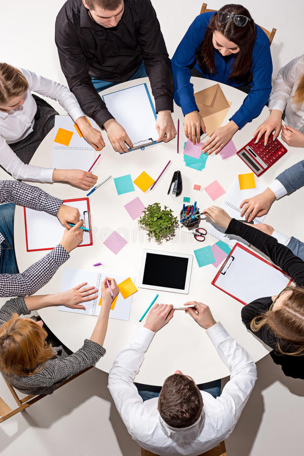 Team o assento atrás da mesa, verificando os relatórios, falando Vista superior fotografia de stock