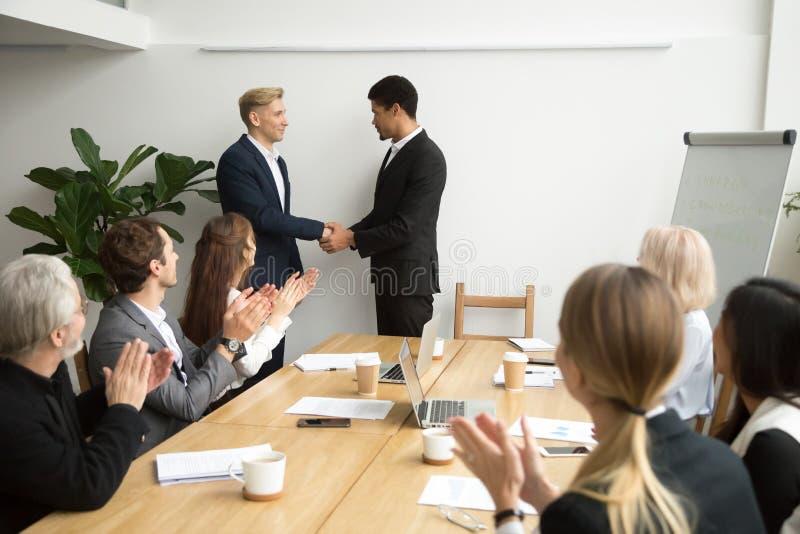 Team o CEO preto de aplauso de apoio e a agitação branca do empregado fotografia de stock