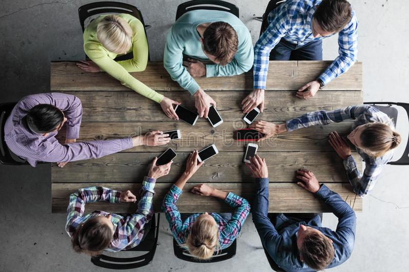 Team of people put smartphones to table royalty free stock image