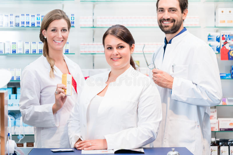 Team of pharmacists in drug store checking pharmaceuticals royalty free stock photography