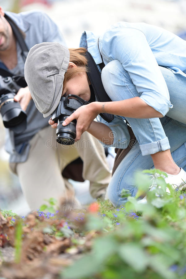 Team of photographers taking photos of flowers. Photographers in park shooting vegetation stock photos