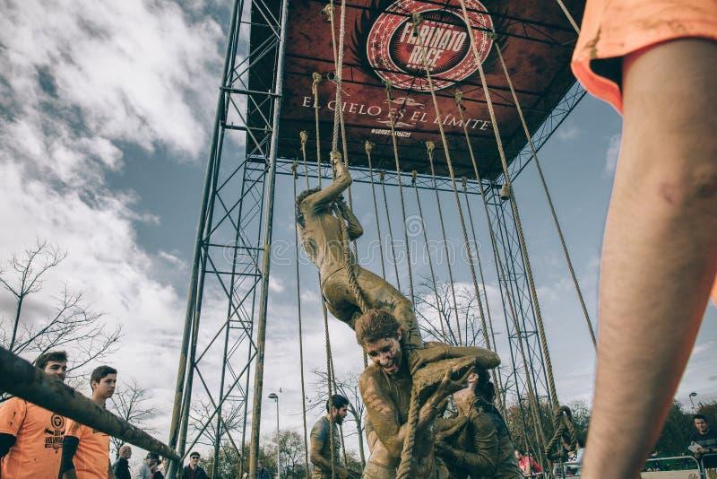 Team portionkvinnan till att klättra repet i ett prov av hinderloppet arkivfoto