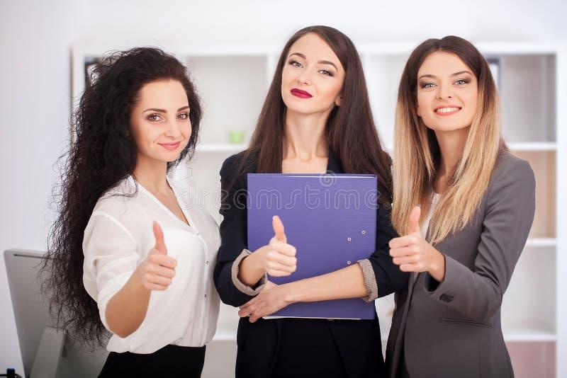 Team Porträt von den glücklichen Geschäftsfrauen, die auf Bürokorridor stehen lizenzfreie stockbilder
