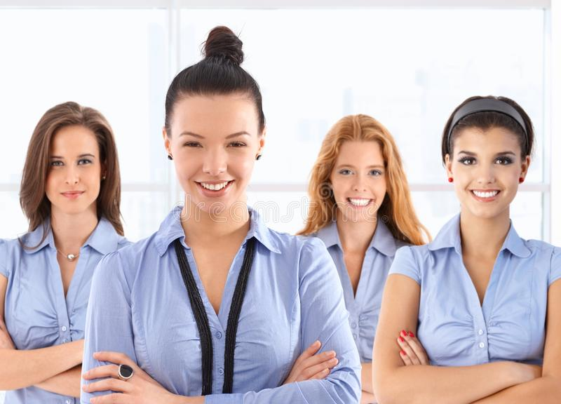 Female front office workers in uniform. Team portrait of attractive young female front office workers in blue uniform, looking at camera, smiling stock photos