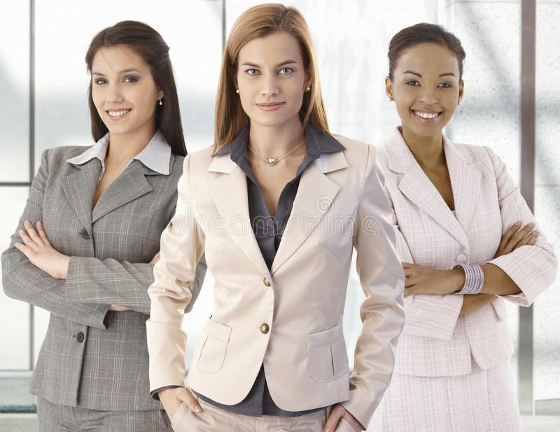 Team portrait of happy businesswomen in office. Team portrait of happy businesswomen standing on office corridor, looking at camera, smiling royalty free stock photos