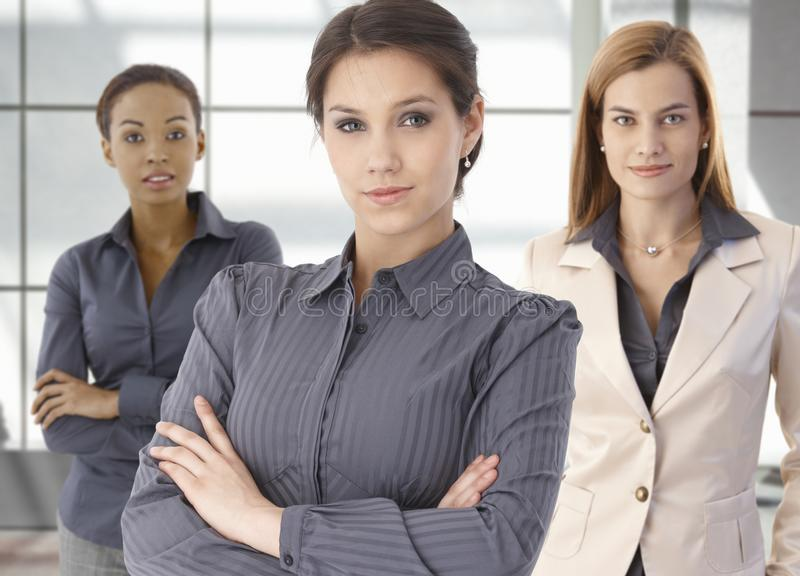 Team portrait of happy businesswomen in office. Team portrait of happy businesswomen standing on office corridor, looking at camera, smiling stock images