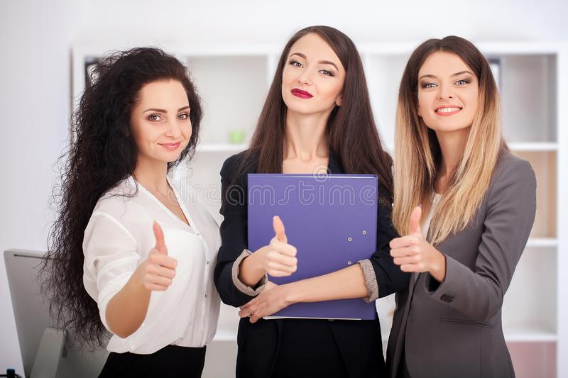 Team portrait of happy businesswomen standing on office corridor royalty free stock images