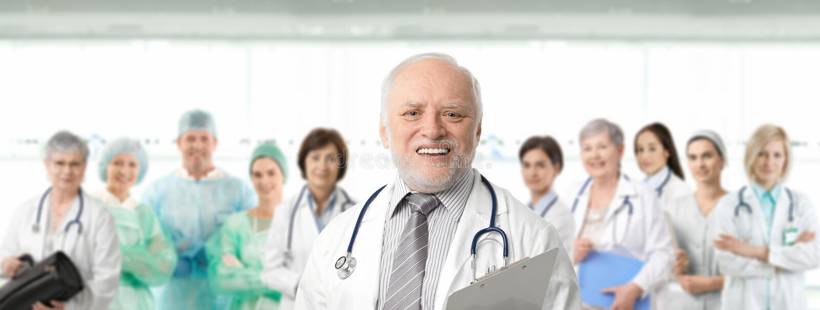 Team portrait of medical professionals. Team of medical professionals lead by senior white haired doctor looking at camera, smiling stock photo