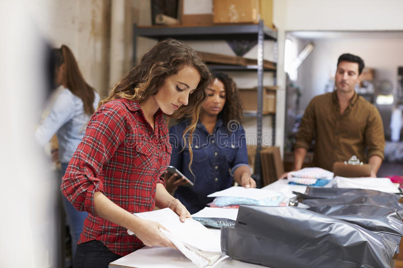 Team in a post room packing clothes orders for distribution royalty free stock images
