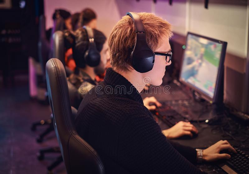 A team of professional cyber sportmans, trains for the championship, plays in a multiplayer video game on pc in a gaming. Club stock photos