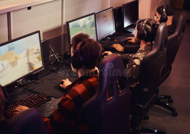A team of professional cyber sportmans, trains for the championship, plays in a multiplayer video game on pc in a gaming. Club royalty free stock image