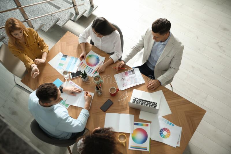 Team of professional designers working together at table. In office stock photo