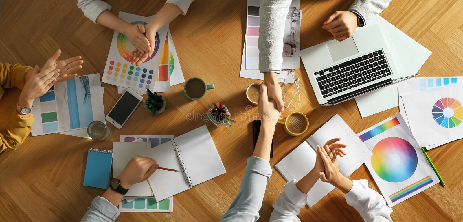 Team of professional designers working together at table stock photos