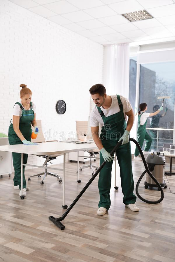 Team of professional janitors working in office. Cleaning service stock images