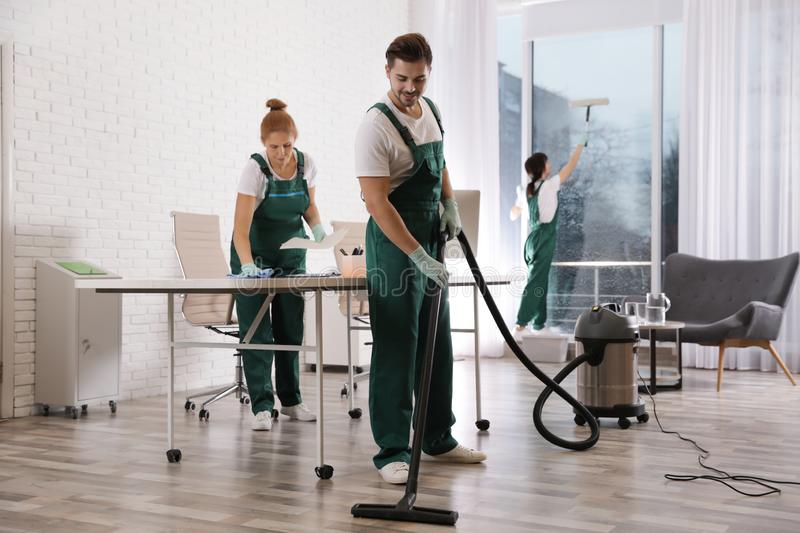 Team of professional janitors working in office. Cleaning service stock image