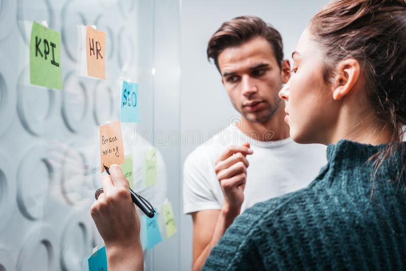 Business colleagues discussing new ideas and using sticky glass note wall. Team of project managers having meeting at modern office. Business colleagues royalty free stock photo