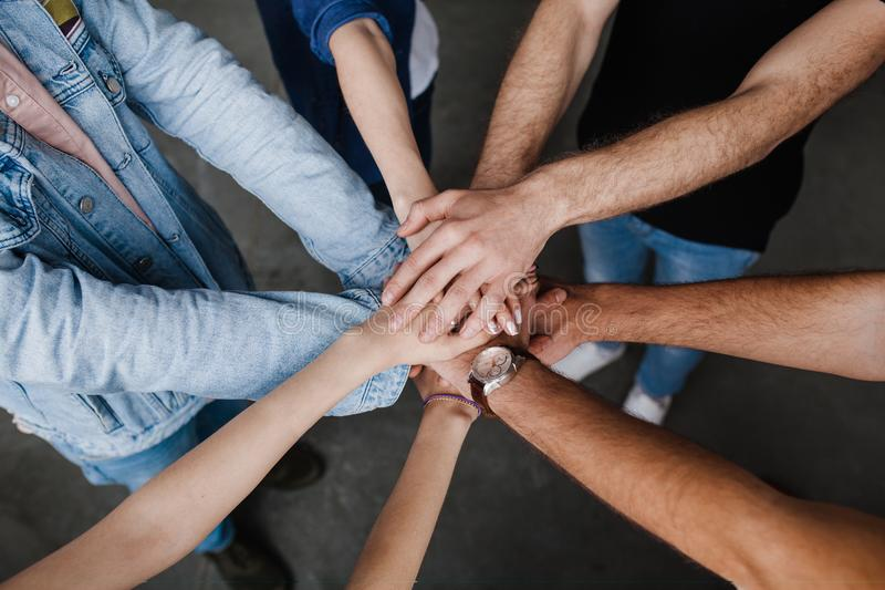 Team put hands together, show connection and alliance, Teambuilding in office, young businessmen and women in casual stock photo